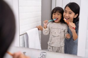 a parent and their child brushing their teeth together to maintain good oral health