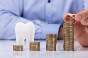 Coins and model tooth symbolizing how to maximize dental insurance benefits