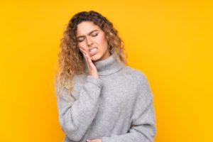 Woman in gray sweater against a yellow background holding the side of her mouth in pain