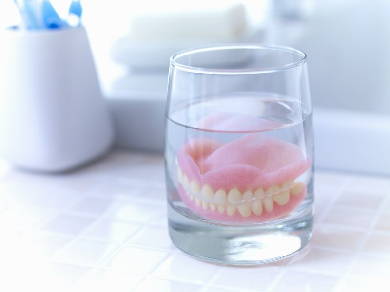 Dentures soaking in a glass