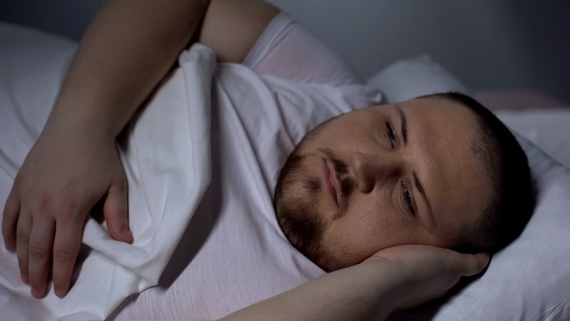 an overweight man lying awake at night because of insomnia caused by weight gain and sleep apnea in Parsippany